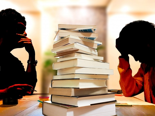 頭を抱えて勉強する男性