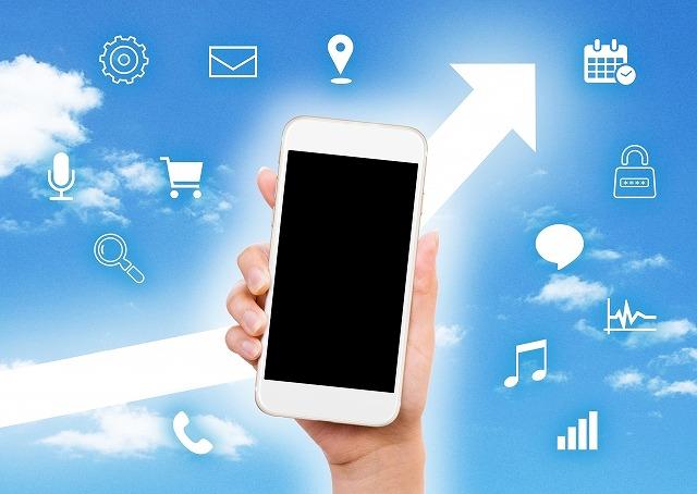 スマートフォンを持つ手と上昇するグラフ