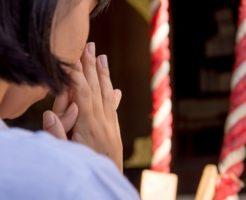 神社でお祈りをする女性